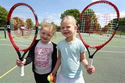 Photo of two girls playing tennis