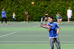 Photo of a child playing tennis