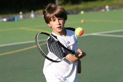 Photo of a boy playing tennis