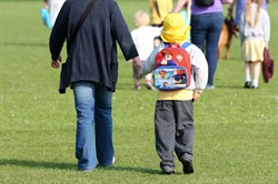 Photo of a child and a parent walking to school
